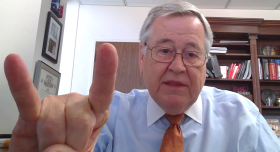 A man with glasses throwing up the Hook 'em Horns hand gesture