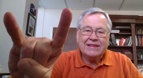 A man smiling and giving the Hook 'em Horns hand gesture.