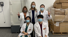 Five people in lab coats wearing masks.