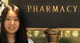 "A woman smiling in front of a sign that says ""Pharmacy."""